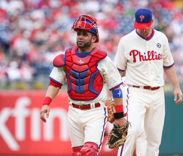 May 18, 2014; Philadelphia, PA, USA; Philadelphia Phillies catcher Wil Nieves (21) lifts his mask and walks back to the plate after talking on the mound with starting pitcher Cliff Lee (33) in a game against the Cincinnati Reds at Citizens Bank Park. The Phillies won 8-3. Mandatory Credit: Bill Streicher-USA TODAY Sports
