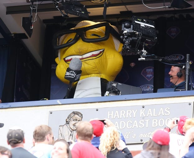 """May 18, 2014; Philadelphia, PA, USA; Zooperstars mascot Harry Canary sings """"take me out to the ballgame"""" from the Harry Kalas broadcast booth between innings of a game at Citizens Bank Park. The Phillies won 8-3. Mandatory Credit: Bill Streicher-USA TODAY Sports"""