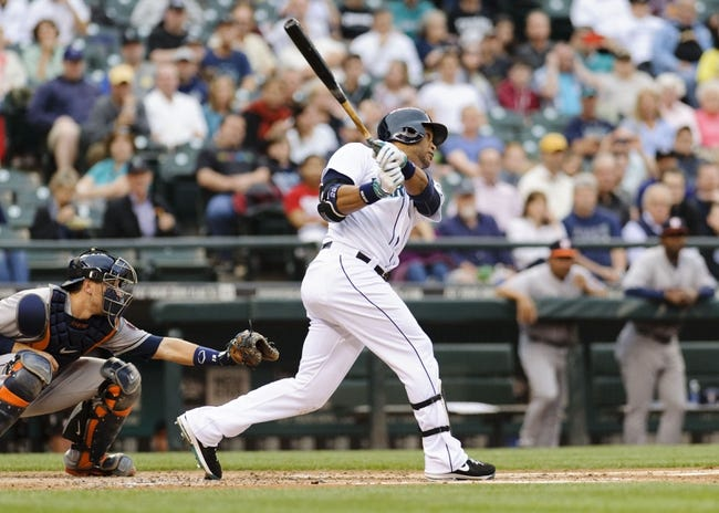 May 22, 2014; Seattle, WA, USA; Seattle Mariners second baseman Robinson Cano (22) hits a RBI sacrifice fly ball against the Houston Astros during the first inning at Safeco Field. Mandatory Credit: Steven Bisig-USA TODAY Sports