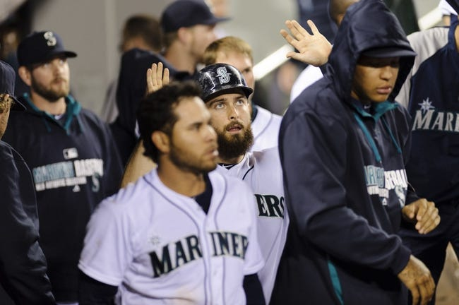 May 22, 2014; Seattle, WA, USA; Seattle Mariners left fielder Dustin Ackley (13) celebrates in the dugout after scoring a run off a 2-RBI single hit against the Houston Astros during the seventh inning at Safeco Field. Mandatory Credit: Steven Bisig-USA TODAY Sports