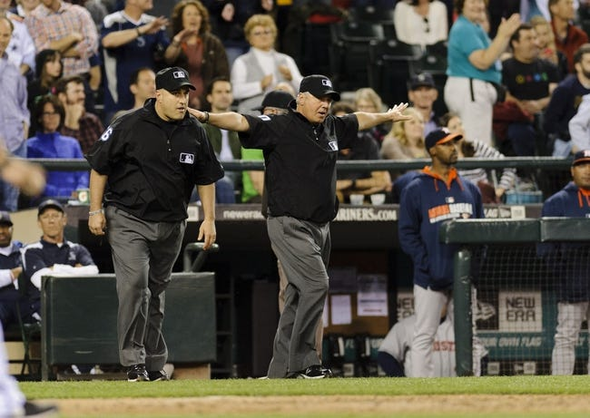 May 22, 2014; Seattle, WA, USA; Third base umpire Tom Hallion (20) calls Seattle Mariners right fielder Michael Saunders (55) (not pictured) safe at first base after an instant replay during the seventh inning between the Seattle Mariners and the Houston Astros at Safeco Field. The play resulted in two Seattle Mariners runs scored. Mandatory Credit: Steven Bisig-USA TODAY Sports