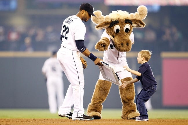 May 25, 2014; Seattle, WA, USA;  Seattle Mariners second baseman Robinson Cano (22) and the moose mascot hand second base to a young fan in between innings during the game against the Houston Astros at Safeco Field. Mandatory Credit: Joe Nicholson-USA TODAY Sports