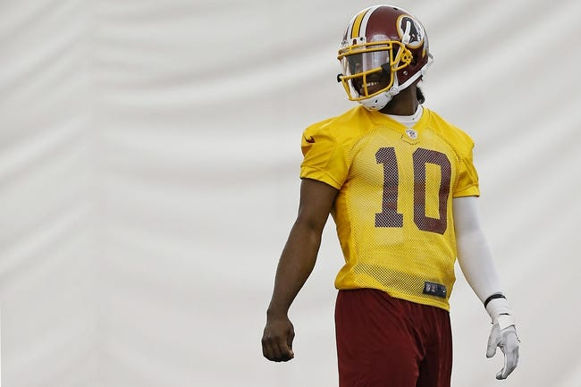 May 29, 2014; Ashburn, VA, USA; Washington Redskins quarterback Robert Griffin III (10) smiles while standing on the field during organized team activities at Redskins Park. Mandatory Credit: Geoff Burke-USA TODAY Sports