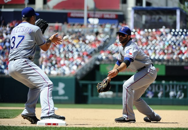 May 31, 2014; Washington, DC, USA; Texas Rangers first baseman Mitch Moreland (18) flips the ball to Texas Rangers relief pitcher Shawn Tolleson (37) for an out against the Washington Nationals during the seventh inning at Nationals Park. Mandatory Credit: Brad Mills-USA TODAY Sports