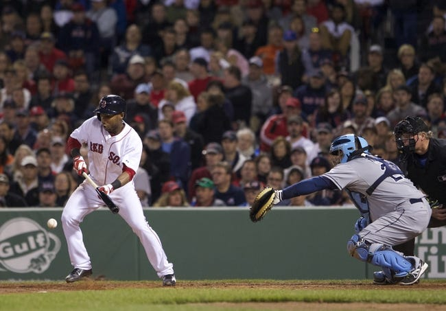 May 31, 2014; Boston, MA, USA; Boston Red Sox second baseman Jonathan Herrera (10) bunts to drive in a run against the Tampa Bay Rays in the fourth inning at Fenway Park. Mandatory Credit: David Butler II-USA TODAY Sports