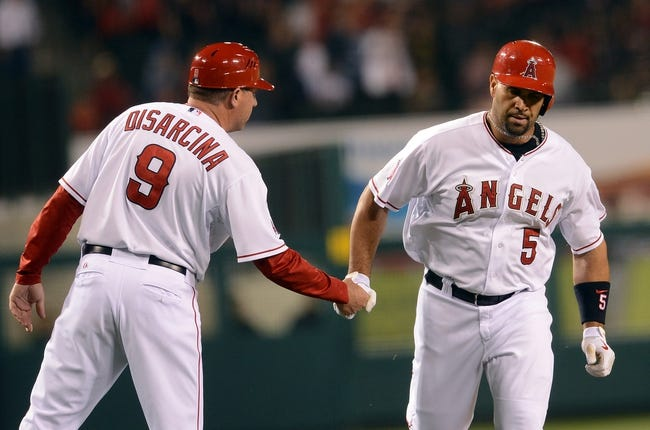 Jun 6, 2014; Anaheim, CA, USA; Los Angeles Angels first baseman Albert Pujols (5) shakes hands with third base coach Gary DiSarcina (9) after a solo home run in the eighth inning of the game against the Chicago White Sox at Angel Stadium of Anaheim. Angels won 8-4. Mandatory Credit: Jayne Kamin-Oncea-USA TODAY Sports