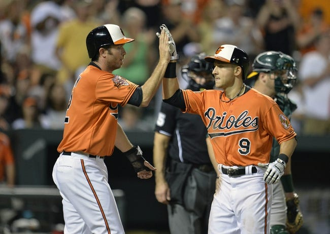 Jun 7, 2014; Baltimore, MD, USA; Baltimore Orioles left fielder David Lough (9) is congratulated by J.J. Hardy (2) after hitting a two-run home run in the sixth inning against the Oakland Athletics at Oriole Park at Camden Yards. The Orioles defeated the Athletics 6-3. Mandatory Credit: Joy R. Absalon-USA TODAY Sports