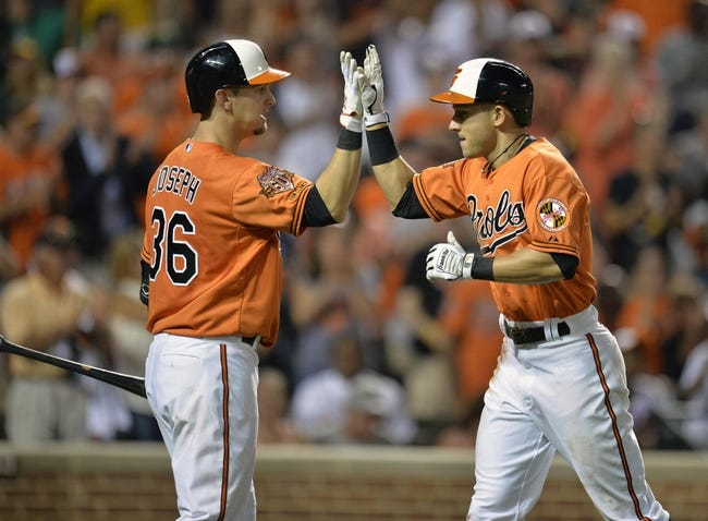Jun 7, 2014; Baltimore, MD, USA; Baltimore Orioles left fielder David Lough (9) is congratulated by Caleb Joseph (36) after hitting a two-run home run in the sixth inning against the Oakland Athletics at Oriole Park at Camden Yards. The Orioles defeated the Athletics 6-3. Mandatory Credit: Joy R. Absalon-USA TODAY Sports
