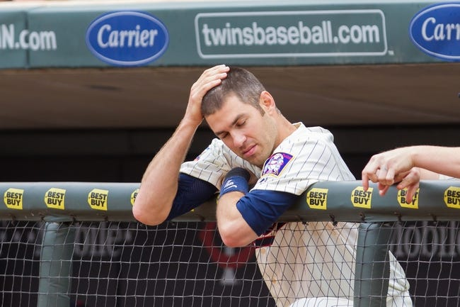 Jun 7, 2014; Minneapolis, MN, USA; Minnesota Twins first baseman Joe Mauer (7) watches from the dugout against the Houston Astros at Target Field. Mandatory Credit: Brad Rempel-USA TODAY Sports