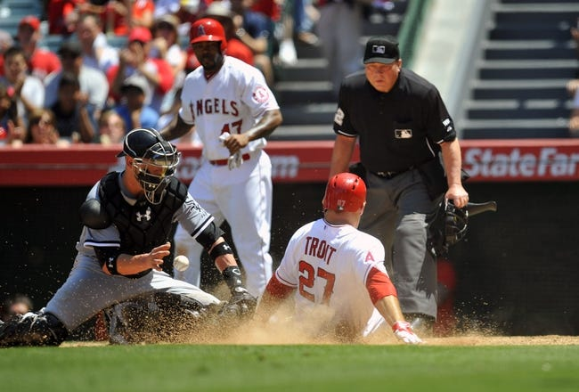 June 8, 2014; Anaheim, CA, USA; Los Angeles Angels center fielder Mike Trout (27) scores a run past  Chicago White Sox catcher Tyler Flowers (21) in the fifth inning at Angel Stadium of Anaheim. Mandatory Credit: Gary A. Vasquez-USA TODAY Sports