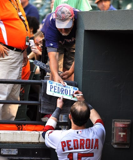 Jun 9, 2014; Baltimore, MD, USA; Boston Red Sox manager second baseman Dustin Pedroia (15) signs an autograph for Doug Hackey from Martha's Vineyard prior to a game against the Baltimore Orioles at Oriole Park at Camden Yards. Mandatory Credit: Joy R. Absalon-USA TODAY Sports