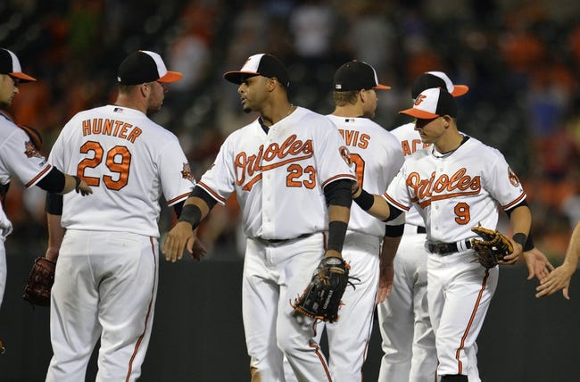 Jun 9, 2014; Baltimore, MD, USA; Baltimore Orioles teammates Tommy Hunter (29) Nelson Cruz (23) Chris Davis (19) and David Lough (9) celebrate after a game against the Boston Red Sox at Oriole Park at Camden Yards. The Orioles defeated the Red Sox 4-0. Mandatory Credit: Joy R. Absalon-USA TODAY Sports