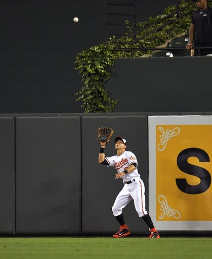 Jun 9, 2014; Baltimore, MD, USA; Baltimore Orioles center fielder David Lough (9) catches a pop-up by Boston Red Sox first baseman Mike Napoli (not shown) in the seventh inning at Oriole Park at Camden Yards. The Orioles defeated the Red Sox 4-0. Mandatory Credit: Joy R. Absalon-USA TODAY Sports