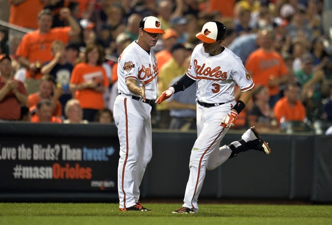 Jun 9, 2014; Baltimore, MD, USA; Baltimore Orioles second baseman Ryan Flaherty (3) is congratulated by third base coach Bobby Dickerson (11) after hitting a solo home run in the seventh inning against the Boston Red Sox at Oriole Park at Camden Yards. The Orioles defeated the Red Sox 4-0. Mandatory Credit: Joy R. Absalon-USA TODAY Sports