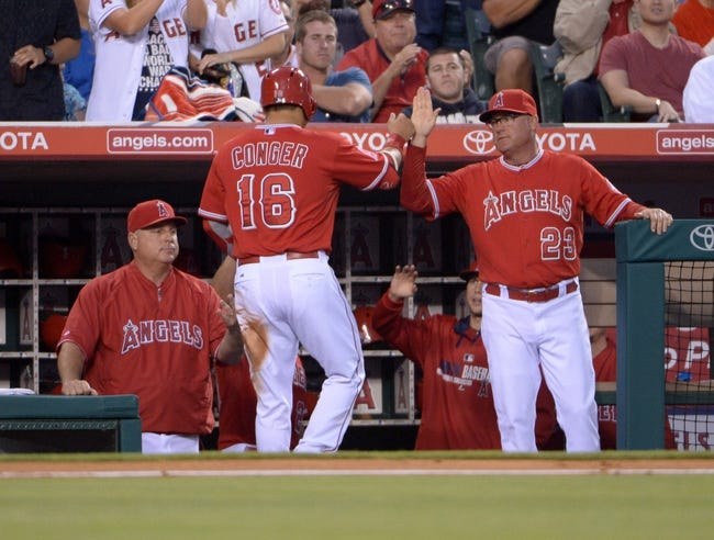 Jun 9, 2014; Anaheim, CA, USA; Los Angeles Angels catcher Hank Conger (16) is greeted by manager Mike Scioscia (left) and pitching coach Mike Butcher (23) after scoring in the third inning against the Oakland Athletics at Angel Stadium of Anaheim. Mandatory Credit: Kirby Lee-USA TODAY Sports