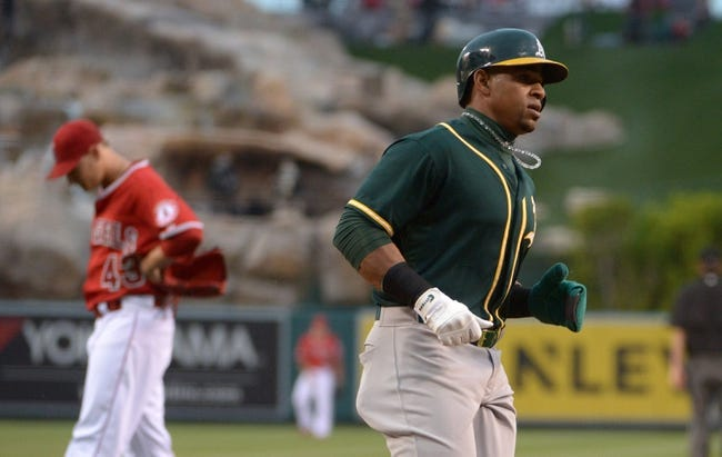 Jun 9, 2014; Anaheim, CA, USA; Oakland Athletics left fielder Yoenis Cespedes (52) crosses home plate to score in the second inning as Los Angeles Angels pitcher Garrett Richards (43) reacts Angel Stadium of Anaheim. Mandatory Credit: Kirby Lee-USA TODAY Sports