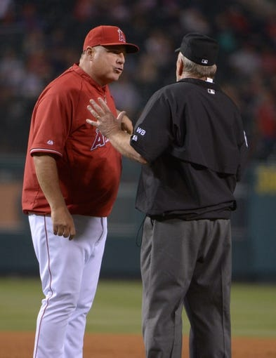 Jun 9, 2014; Anaheim, CA, USA; Los Angeles Angels manager Mike Scioscia (left) is ejected after arguing with first base umpire Bob Davidson (61) in the fifth inning against the Oakland Athletics at Angel Stadium of Anaheim. Mandatory Credit: Kirby Lee-USA TODAY Sports