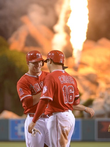 Jun 9, 2014; Anaheim, CA, USA; Los Angeles Angels center fielder Mike Trout (27) is congratulated by catcher Hank Conger (16) after a ground-rule double because of fan interference in the fifth inning against the Oakland Athletics at Angel Stadium of Anaheim. Mandatory Credit: Kirby Lee-USA TODAY Sports
