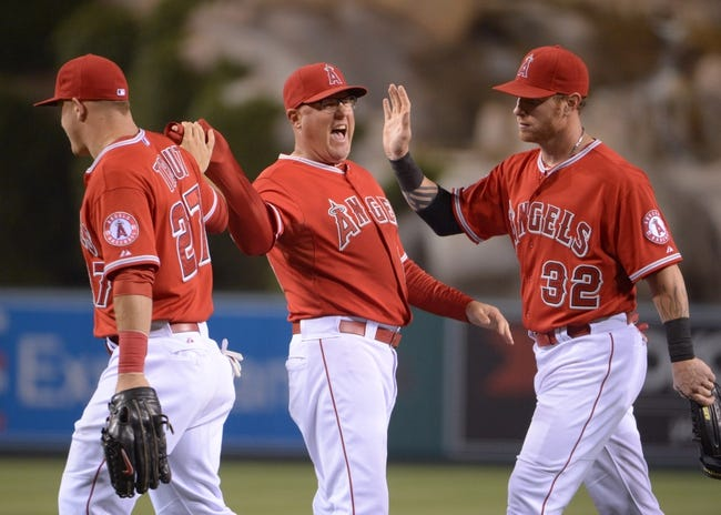 Jun 9, 2014; Anaheim, CA, USA; Los Angeles Angels pitching coach Mike Butcher (center) congratulates center fielder Mike Trout (left) and left fielder Josh Hamilton (32) after the game against the Oakland Athletics at Angel Stadium of Anaheim. The Angels defeated the Athletics 4-1. Mandatory Credit: Kirby Lee-USA TODAY Sports