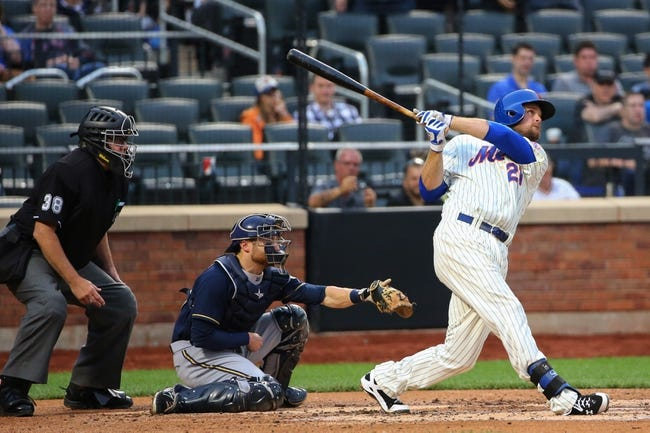 Jun 11, 2014; New York, NY, USA;  New York Mets first baseman Lucas Duda (21) hits a sacrifice fly to center allowing right fielder Curtis Granderson (3) (not pictured) to score during the second inning against the Milwaukee Brewers at Citi Field. Mandatory Credit: Anthony Gruppuso-USA TODAY Sports