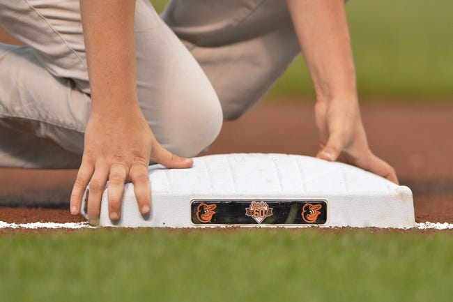 Jun 11, 2014; Baltimore, MD, USA;  The grounds crew ensures third base is secure prior to the game between the Boston Red Sox and Baltimore Orioles at Oriole Park at Camden Yards. Mandatory Credit: Tommy Gilligan-USA TODAY Sports