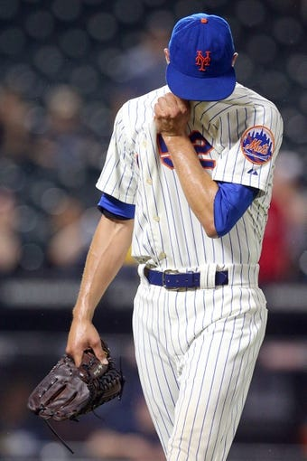 Jun 12, 2014; New York, NY, USA; New York Mets relief pitcher Carlos Torres (52) reacts as he's taken out of the game against the Milwaukee Brewers during the thirteenth inning at Citi Field. The Brewers won 5-1 in thirteen innings. Mandatory Credit: Brad Penner-USA TODAY Sports