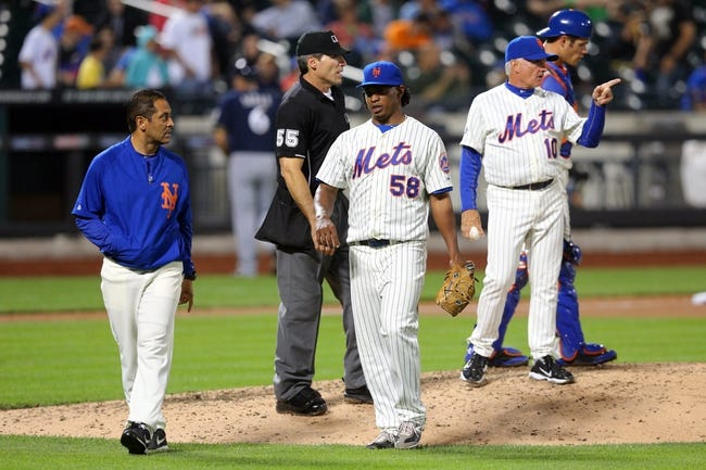 Jun 12, 2014; New York, NY, USA; New York Mets relief pitcher Jenrry Mejia (58) is taken out of the game against the Milwaukee Brewers with an injury during the eleventh inning at Citi Field. The Brewers won 5-1 in thirteen innings. Mandatory Credit: Brad Penner-USA TODAY Sports