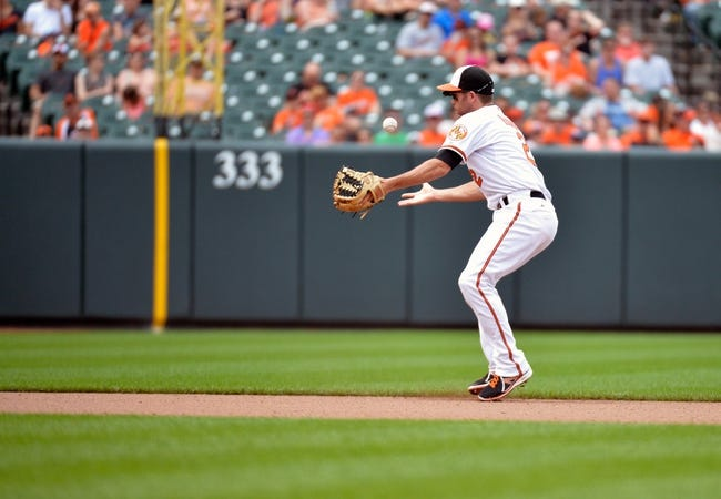 Jun 8, 2014; Baltimore, MD, USA; Baltimore Orioles shortstop J.J. Hardy (2) bobbles a ground ball in the seventh inning against the Oakland Athletics at Oriole Park at Camden Yards. The Athletics defeated the Orioles 11-1. Mandatory Credit: Joy R. Absalon-USA TODAY Sports