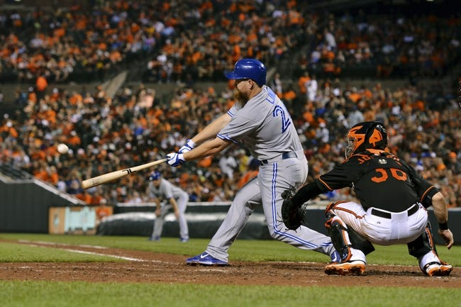 Jun 13, 2014; Baltimore, MD, USA; Toronto Blue Jays designated hitter Adam Lind (26) singles during the inning  sixth at Oriole Park against the Baltimore Orioles  at Camden Yards. Mandatory Credit: Tommy Gilligan-USA TODAY Sports