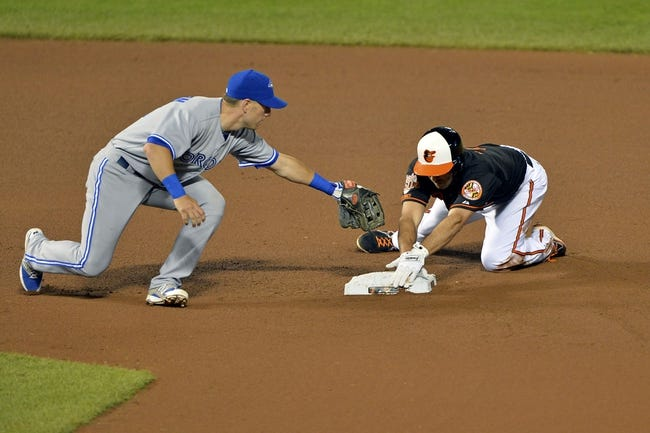 Jun 13, 2014; Baltimore, MD, USA; Baltimore Orioles shortstop J.J. Hardy (2) slides under Toronto Blue Jays second baseman Steve Tolleson (18) for a double during sixth the inning  at Oriole Park at Camden Yards. Mandatory Credit: Tommy Gilligan-USA TODAY Sports