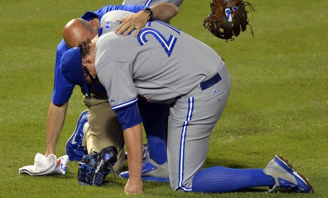 Jun 13, 2014; Baltimore, MD, USA; Toronto Blue Jays head trainer George Poulis tends to relief pitcher Brett Cecil (27) after he goes to a knee during the eighth inning inning against the Baltimore Orioles at Oriole Park at Camden Yards. Toronto Blue Jays defeated Baltimore Orioles 4-0. Mandatory Credit: Tommy Gilligan-USA TODAY Sports