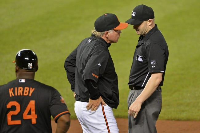 Jun 13, 2014; Baltimore, MD, USA; Baltimore Orioles manager Buck Showalter (26) speaks with umpire Mike Estabrook (83) prior to challenging left fielder Nelson Cruz (23) being called out at first during the eighth inning  inning against the Toronto Blue Jays at Oriole Park at Camden Yards. Toronto Blue Jays defeated Baltimore Orioles 4-0. Mandatory Credit: Tommy Gilligan-USA TODAY Sports