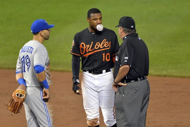 Jun 13, 2014; Baltimore, MD, USA; Toronto Blue Jays right fielder Jose Bautista (19) and Baltimore Orioles center fielder Adam Jones (10) speaks with umpire Hunter Wendelstedt (21) during a challenge in the eighth inning    at Oriole Park at Camden Yards. Toronto Blue Jays defeated Baltimore Orioles 4-0. Mandatory Credit: Tommy Gilligan-USA TODAY Sports
