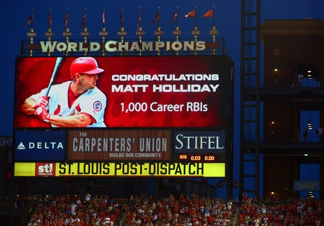Jun 16, 2014; St. Louis, MO, USA; St. Louis Cardinals left fielder Matt Holliday (7) is honored after driving in his 1,000 career RBI during the fifth inning against the New York Mets at Busch Stadium. Mandatory Credit: Jeff Curry-USA TODAY Sports