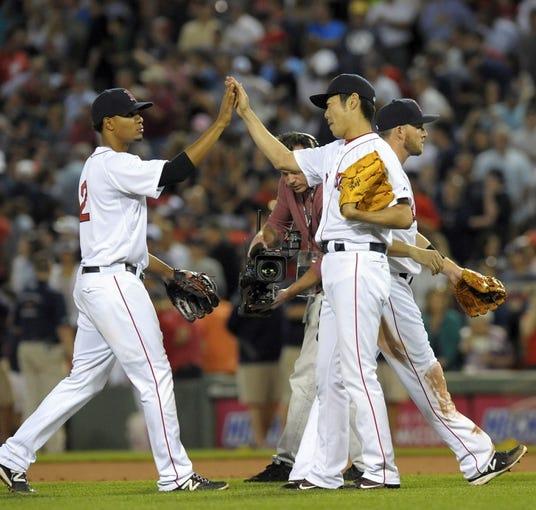 Jun 16, 2014; Boston, MA, USA; Boston Red Sox third baseman Xander Bogaerts (2) high fives relief pitcher Koji Uehara (19) after defeating the Minnesota Twins at Fenway Park. Mandatory Credit: Bob DeChiara-USA TODAY Sports