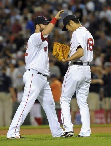 Jun 16, 2014; Boston, MA, USA; Boston Red Sox first baseman Mike Napoli (12) congratulates relief pitcher Koji Uehara (19) after defeating the Minnesota Twins at Fenway Park. Mandatory Credit: Bob DeChiara-USA TODAY Sports