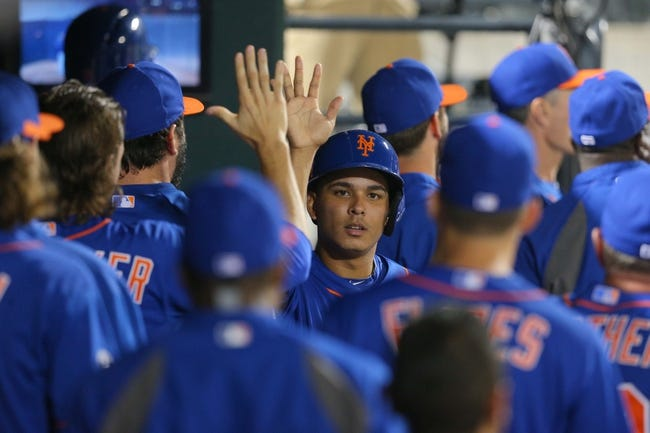 Jun 13, 2014; New York, NY, USA; New York Mets shortstop Ruben Tejada (11) is congratulated in the dugout after scoring a run against the San Diego Padres during the seventh inning of a game at Citi Field. The Mets defeated the Padres 6-2. Mandatory Credit: Brad Penner-USA TODAY Sports