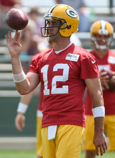 Jun 17, 2014; Green Bay, WI, USA; Green Bay Packers quarterback Aaron Rodgers spins a ball on his finger during the team's minicamp at Ray Nitschke Field. Mandatory Credit: Benny Sieu-USA TODAY Sports