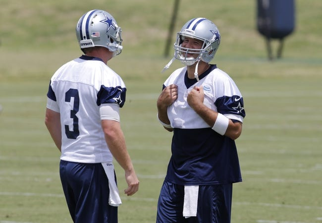 Jun 17, 2014; Dallas, TX, USA; Dallas Cowboys quarterback Tony Romo (9) smiles as he hides jersey number 7 he borrowed from Caleb Hanie (not pictured) as he talks to Brandon Weeden (3) during minicamp at Cowboys headquarters at Valley Ranch. Mandatory Credit: Matthew Emmons-USA TODAY Sports