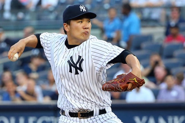 Jun 17, 2014; Bronx, NY, USA; New York Yankees starting pitcher Masahiro Tanaka (19) pitches during the first inning against the Toronto Blue Jays at Yankee Stadium. Mandatory Credit: Anthony Gruppuso-USA TODAY Sports