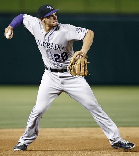 May 7, 2014; Arlington, TX, USA; Colorado Rockies third baseman Nolan Arenado (28) throws to first base on a ground-out hit by a Texas Rangers right fielder during the fifth inning of a baseball game at Globe Life Park in Arlington. Mandatory Credit: Jim Cowsert-USA TODAY Sports