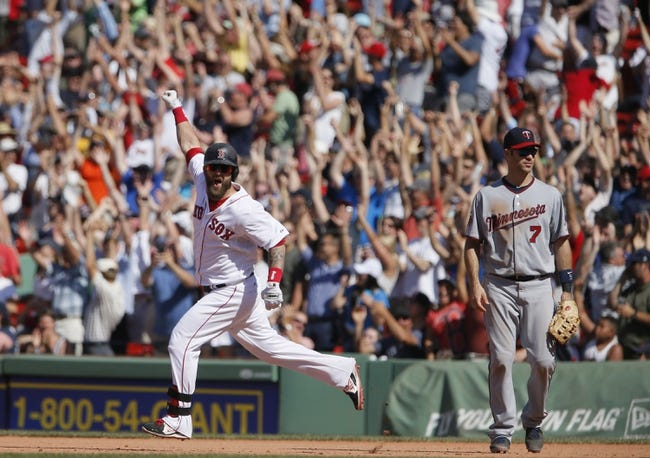 Jun 18, 2014; Boston, MA, USA; Boston Red Sox first baseman Mike Napoli (left) reacts after hitting the game winning home run as Minnesota Twins first baseman Joe Mauer (7) looks on in the tenth inning at Fenway Park. The Red Sox defeated the Twins 2-1. Mandatory Credit: David Butler II-USA TODAY Sports