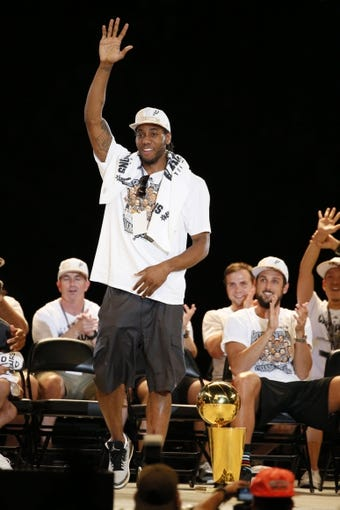 Jun 18, 2014; San Antonio, TX, USA; San Antonio Spurs forward Kawhi Leonard (2) waves to the crowd during NBA championship celebrations at Alamodome. Mandatory Credit: Soobum Im-USA TODAY Sports