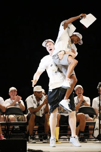 Jun 18, 2014; San Antonio, TX, USA; San Antonio Spurs guard Patrick Mills (8) is lifted up by teammate San Antonio Spurs forward Aron Baynes (16) during NBA championship celebrations at Alamodome. Mandatory Credit: Soobum Im-USA TODAY Sports