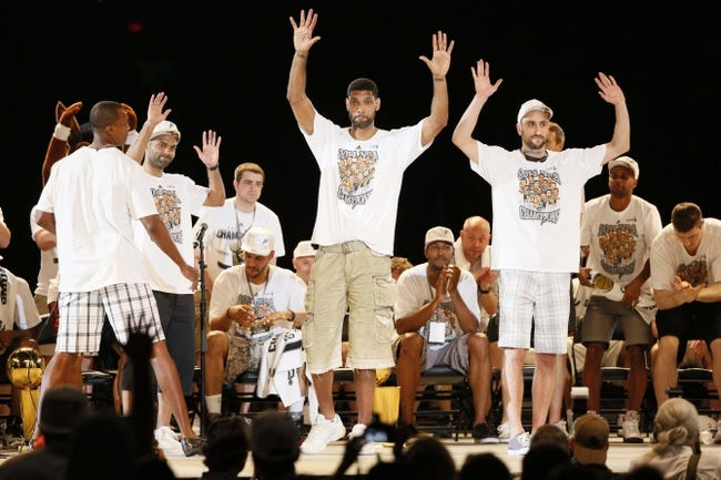 Jun 18, 2014; San Antonio, TX, USA; San Antonio Spurs forward Tim Duncan (middle) and guard Manu Ginobili (right) react to the crowd during NBA championship celebrations at Alamodome. Mandatory Credit: Soobum Im-USA TODAY Sports