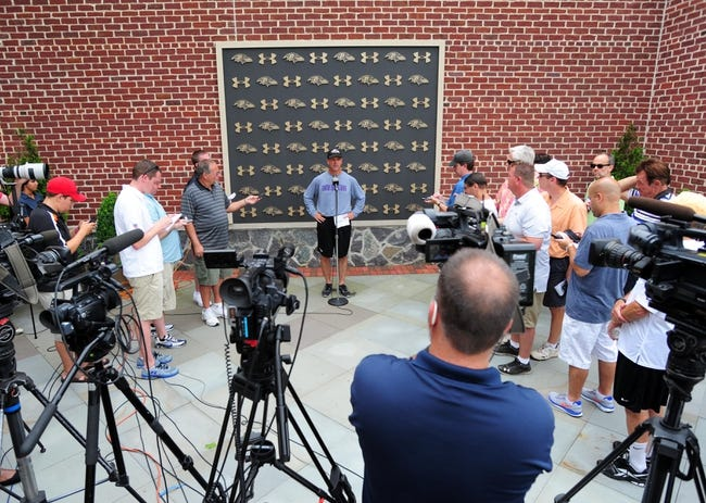 Jun 19, 2014; Baltimore, MD, USA; Baltimore Ravens head coach John Harbaugh (rear center) talks to the media after minicamp at the Under Armour Performance Center. Mandatory Credit: Evan Habeeb-USA TODAY Sports