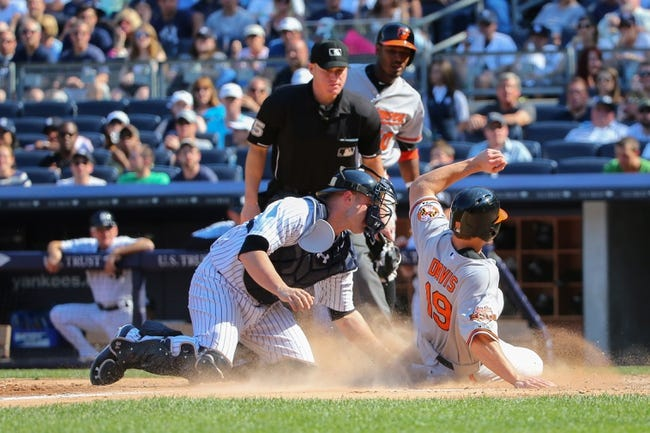 Jun 22, 2014; Bronx, NY, USA;  Baltimore Orioles first baseman Chris Davis (19) slides home to score during the eighth inning against the New York Yankees at Yankee Stadium. Baltimore Orioles won 8-0. Mandatory Credit: Anthony Gruppuso-USA TODAY Sports