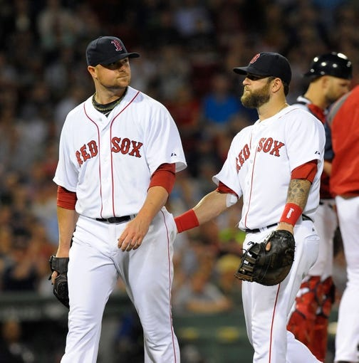 Jun 17, 2014; Boston, MA, USA; Boston Red Sox first baseman Mike Napoli (12) gives starting pitcher Jon Lester (31) a tap after being relieved during the seventh inning at Fenway Park. Mandatory Credit: Bob DeChiara-USA TODAY Sports
