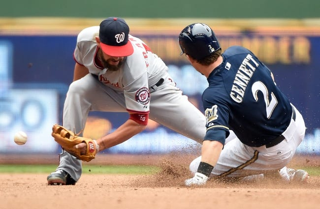 Jun 25, 2014; Milwaukee, WI, USA;  Milwaukee Brewers second baseman Scooter Gennett (2) advances to 2nd base on a fielder's choice after hitting a RBI single in the sixth inning as Washington Nationals second  baseman Kevin Frandsen (19) fields the throw at Miller Park. Mandatory Credit: Benny Sieu-USA TODAY Sports