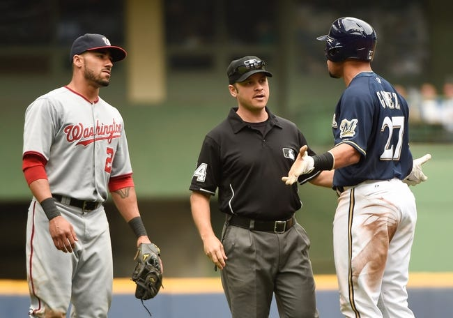 Jun 25, 2014; Milwaukee, WI, USA;  Washington Nationals shortstop Ian Desmond (20) confronts Milwaukee Brewers center fielder Carlos Gomez (27) after Gomez slid hard into second baseman Kevin Frandsen (not pictured) in the eighth inning at Miller Park. MLB umpire Mark Wegner stands in between.  The Brewers beat the Nationals 9-2.  Mandatory Credit: Benny Sieu-USA TODAY Sports